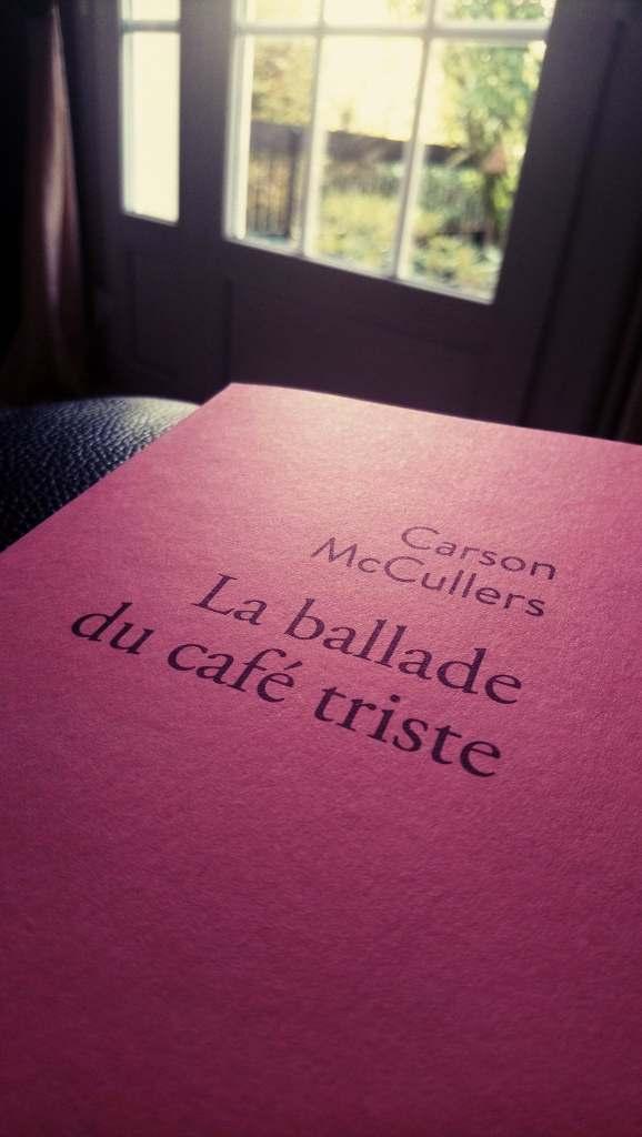 Couverture rose de « La Ballade du café triste » de Carson McCullers, dans l'édition française de Stock, posée sur l'accoudoir d'un canapé avec une fenêtre en fond.